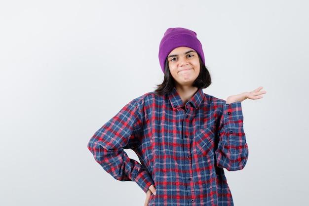 Tienervrouw spreidt handpalm opzij en houdt hand op heup in geruit overhemd