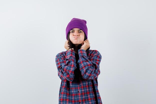 Tienervrouw trekt haar oorlellen naar beneden terwijl ze op wangen blaast in geruit overhemd