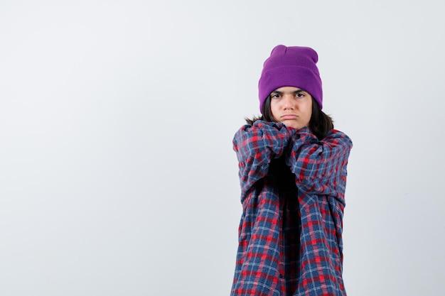 Tienervrouwenmuts die handen achter de nek vasthoudt en er teleurgesteld uitziet