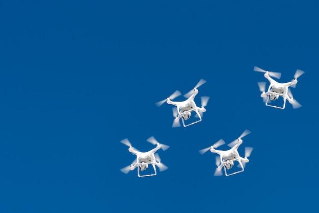 Tientallen drones zwermen in de blauwe lucht. quadcopters drones met digitale camera in de lucht boven de stad.