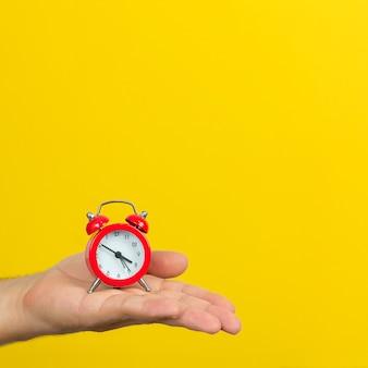Tijd beheer concept. hand met kleine rode wekker op trendy gele kleur achtergrond