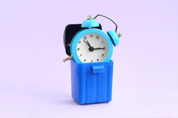 Tijd concept verspillen. wekker in vuilnisbak