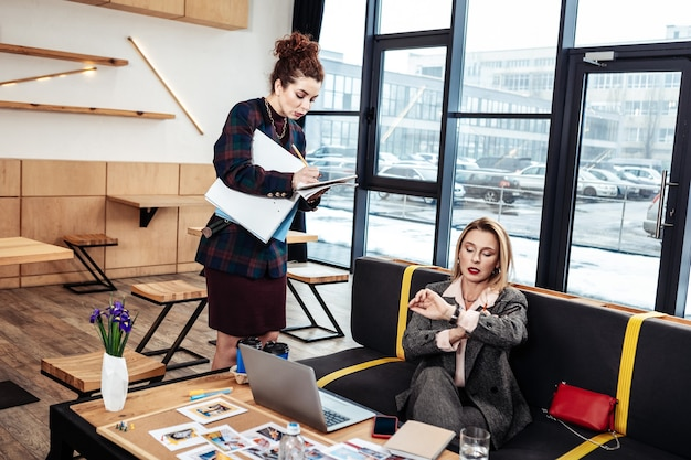 Tijd controleren. drukke blonde zakenvrouw die de tijd controleert op het horloge dat te laat is voor een vergadering