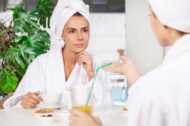 Tijd doorbrengen in de spa. twee mooie jonge vrouwen in badjas die thee drinken en met elkaar praten terwijl ze voor het zwembad zitten