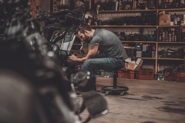 Tijd doorbrengen met fietsen. zelfverzekerde jongeman die motorfiets in reparatiewerkplaats repareert