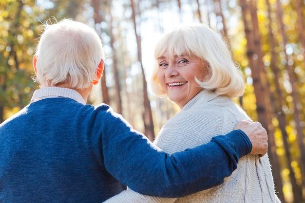 Tijd doorbrengen met man. achteraanzicht van een gelukkige senior vrouw die over de schouder kijkt en glimlacht terwijl ze met haar man door het park loopt