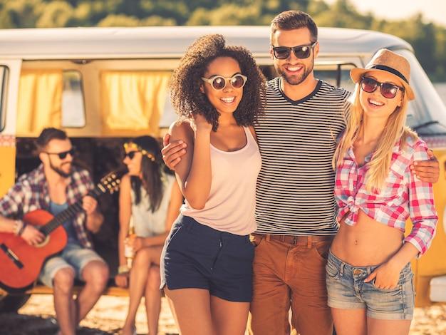 Tijd doorbrengen met vrienden. gelukkige jonge man die twee mooie vrouwen omhelst terwijl een jong stel in een retro minibus op de achtergrond zit