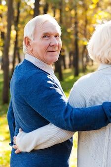 Tijd doorbrengen met vrouw. achteraanzicht van een gelukkige senior man die over de schouder kijkt en glimlacht terwijl hij met zijn vrouw door het park loopt