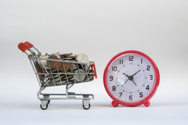 Tijd, e-commerce en winkelconcept. mini-winkelwagentje gevuld met munten met wekker