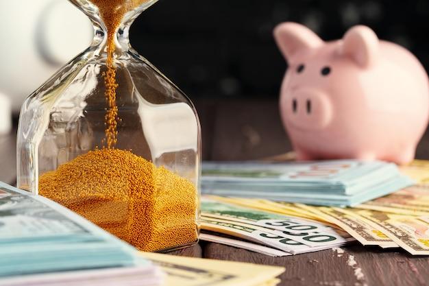 Tijd en geld bedrijfsconcept. zandloper en geld