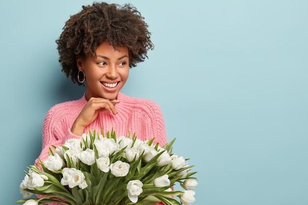 Tijd, goed humeur en etniciteit concept. gelukkig afro-amerikaanse vrouw met krullend haar, kijkt opzij, heeft een zachte glimlach, houdt witte aromatische bloemen, geïsoleerd over blauwe muur, lege ruimte