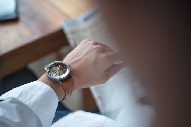 Tijd houden voor belangrijke benoeming, een man kijkt op zijn horloge van serieuze vergadering.