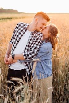 Tijd in stralen van ondergaande zomerzon is gecreëerd voor liefde en tederheid voor een jong zwanger stel. dankbaarheid en geluk. zwangerschap. geluk en tederheid. liefde en aandacht.familiewaarden.