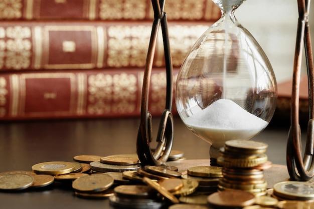 Tijd is geld concept. close up van zandloper met geld munten