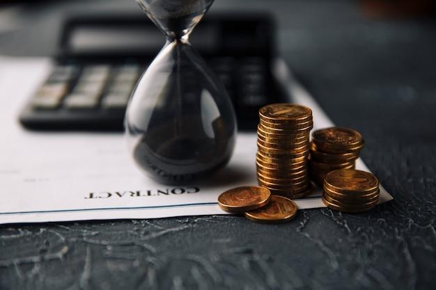 Tijd is geld concept. contract tekenen. munten en zandloper naast de rekenmachine op een contract