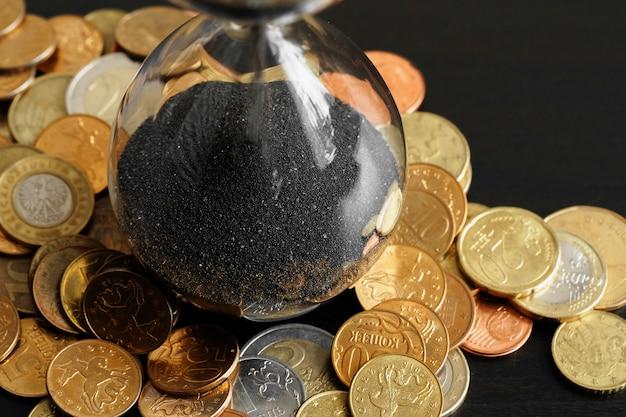 Tijd is geld concept. van zandloper met geldmunten