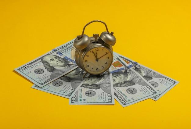Tijd is geld. retro wekker en honderd dollarbiljetten op een gele achtergrond