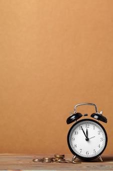Tijd is geld, tafelklok met munten op bruine muurachtergrond