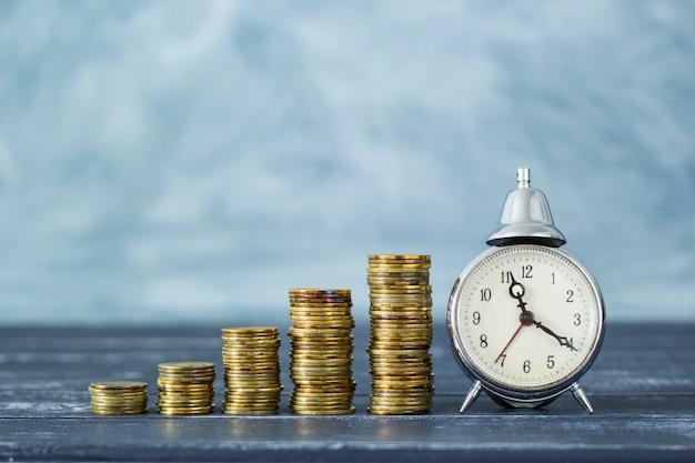 Tijd is geld. wekker en munten - concept van zakelijke financiële ideeën.