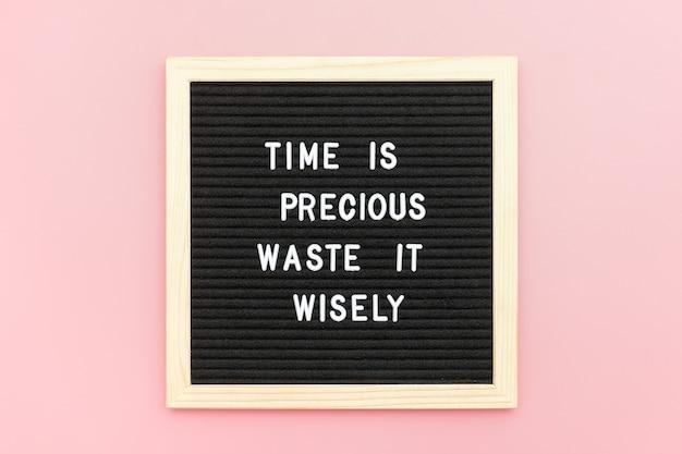 Tijd is kostbaar, verspil het verstandig. motiverende citaat op letterbord op roze achtergrond.