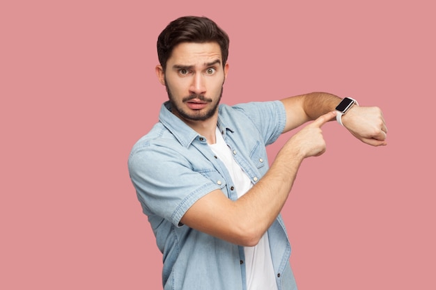 Tijd is op. portret van een serieuze, knappe, bebaarde jongeman in een blauw casual stijlshirt dat staat en naar de camera kijkt, wijzend op zijn slimme horloge. indoor studio opname, geïsoleerd op roze achtergrond.