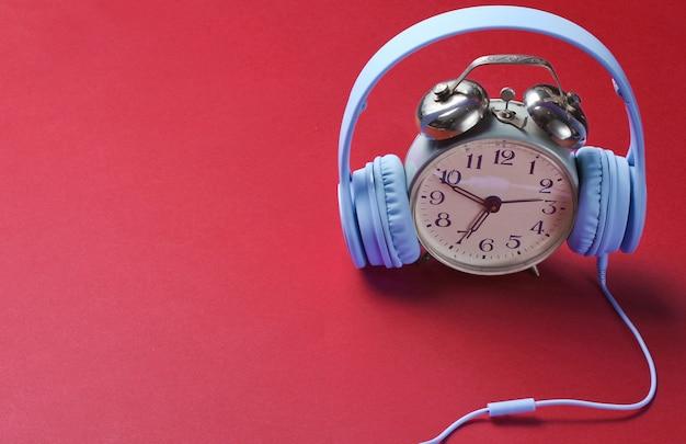 Tijd luisteren naar muziek concept met retro wekker en koptelefoon