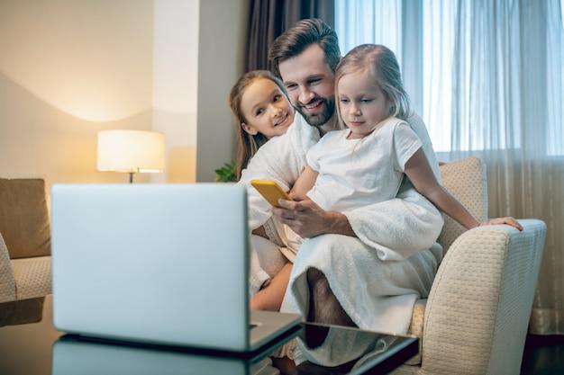 Tijd met familie. jonge, bebaarde man tijd doorbrengen met zijn schattige dochters