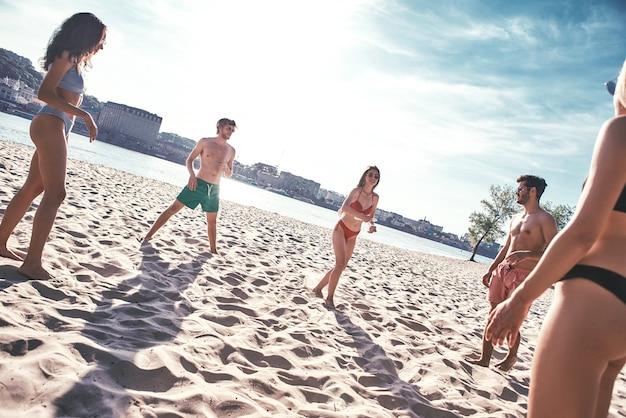Tijd met vriendengroep jonge mensen die freesby spelen op het strand
