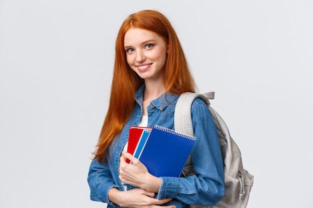 Tijd naar school. mooie vrolijke moderne roodharige vrouw met rugzak met notebooks op weg naar de universiteit, geamuseerd glimlachend, terug naar de klas na de pauze, staande witte achtergrond