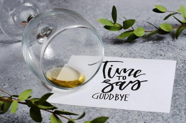Tijd om afscheid te nemen. de inscriptie op een vel wit papier. witte wijn in een glazen glas. concept - verslechtering van de relaties tussen mensen