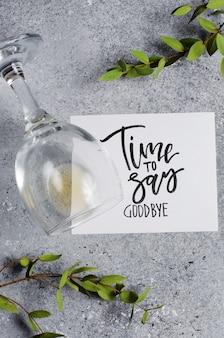 Tijd om afscheid te nemen. de inscriptie op een vel wit papier. witte wijn in een glazen glas.