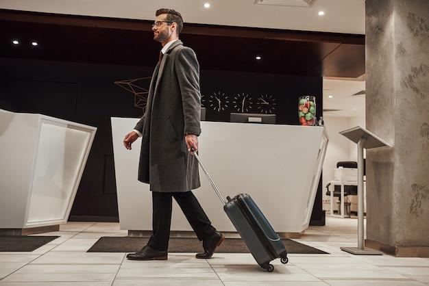 Tijd om dit hotel te boeken. volledige lengte van gelukkige jonge man met reistas die vanaf het vliegveld binnen het hotel loopt. hij is op zoek naar receptioniste
