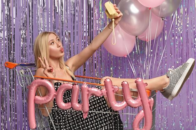 Tijd om een selfie te maken. mooie vrouw met make-up, maakt vredesgebaar, vouwt lippen op camera, poseert in trolley, draagt polka dot jurk, sportschoenen, heeft plezier op vrijgezellenfeest, geniet van vrije tijd en nachtleven