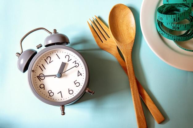 Tijd om gewicht te verliezen, controle te eten of tijd voor een dieet, een wekker met de gezonde decoratie van het hulpmiddelconcept op blauw