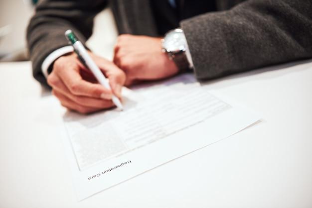 Tijd om het dealcontract te ondertekenen. zakenman vervult en ondertekent contract