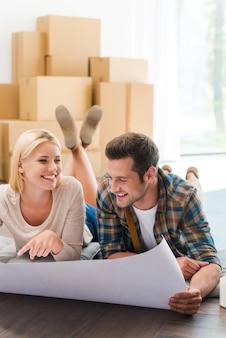 Tijd om hun nieuwe huis te plannen. gelukkig jong stel dat op de vloer van hun nieuwe appartement ligt en door de blauwdruk kijkt terwijl kartonnen dozen op de achtergrond liggen