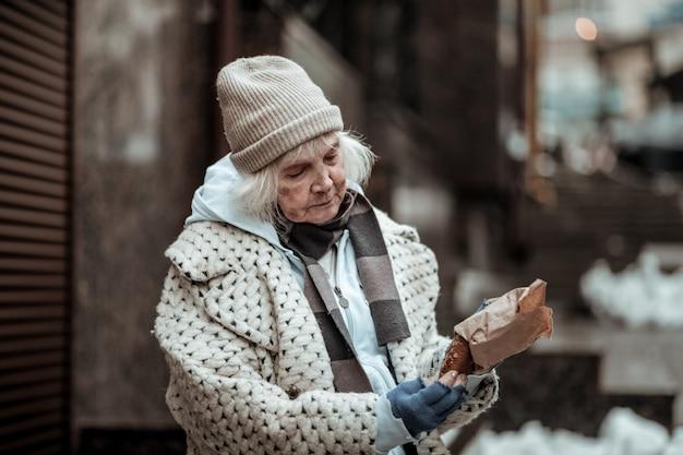 Tijd om te eten. aardige oude vrouw die het insect uit de zak haalt terwijl ze zich klaarmaakt om het op te eten