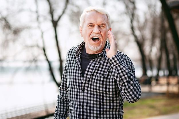 Tijd om te gaan. aantrekkelijke senior man poseren in park en schreeuwen