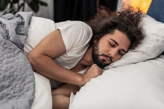 Tijd om te gaan slapen. aangename knappe man die op het kussen ligt terwijl hij wil slapen