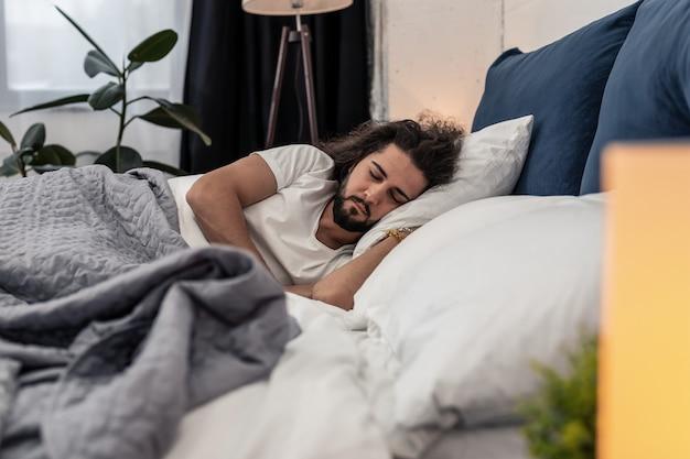 Tijd om te gaan slapen. aardige bebaarde man die in zijn bed slaapt terwijl hij thuis is