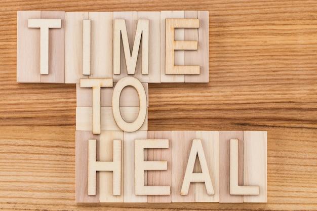 Tijd om te genezen-tekst in vintage letters op houten blokken. geneeskunde concept.