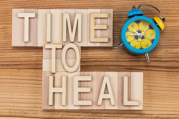 Tijd om te genezen-tekst in vintage letters op houten blokken met wekker. geneeskunde concept.