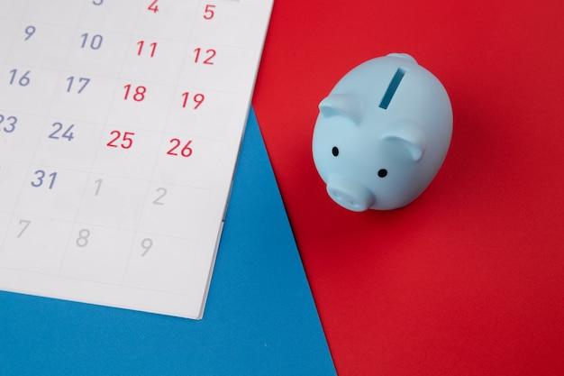 Tijd om te investeren, bedrijfsconcept. blauwe spaarvarken met kalender op kleurrijke achtergrond. bovenaanzicht.