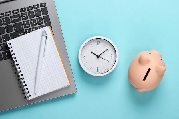 Tijd om te investeren, online zaken. spaarvarken met klok en laptop toetsenbord, notitieboekje op blauwe oppervlakte. bovenaanzicht