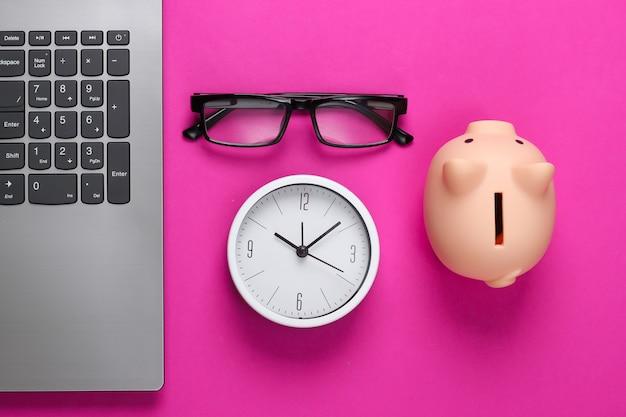Tijd om te investeren, online zaken. spaarvarken met klok, laptop, bril op roze oppervlak. bovenaanzicht