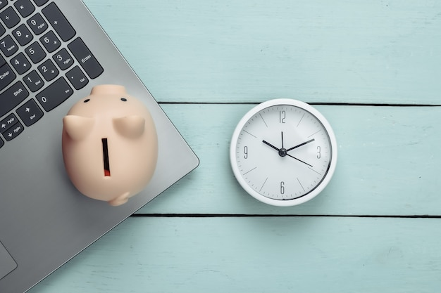 Tijd om te investeren, online zaken. spaarvarken met klok, laptop toetsenbord op blauwe houten oppervlak. bovenaanzicht