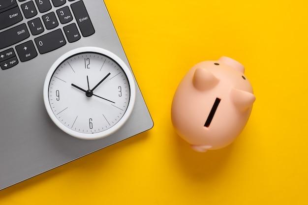Tijd om te investeren, online zaken. spaarvarken met klok op laptop toetsenbord. geel oppervlak. bovenaanzicht