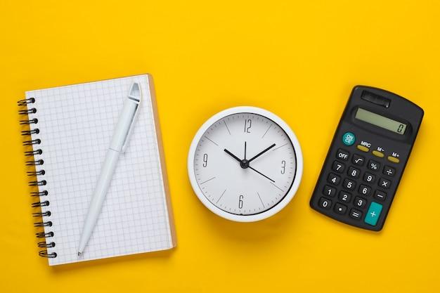 Tijd om te investeren. witte klok, notitieboekje en rekenmachine op gele achtergrond. minimalistisch studio-opname. bovenaanzicht