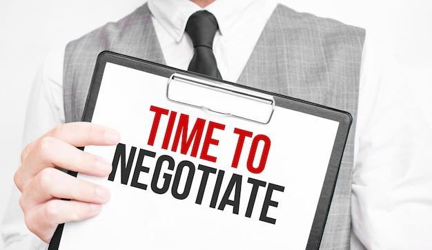 Tijd om te onderhandelen over inscriptie op een notitieboekje in de handen van een zakenman