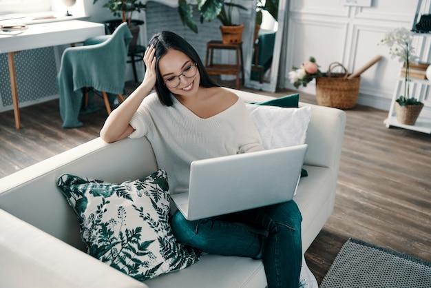 Tijd om te ontspannen. bovenaanzicht van jonge vrouw die laptop gebruikt terwijl ze thuis tijd doorbrengt